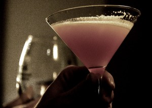 Hand holding aloft a cocktail glass